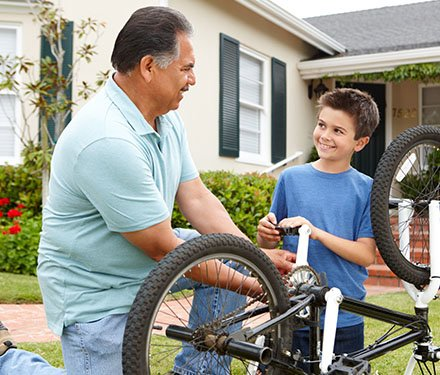 Grandfather kneeling beside his grandson helping him fix a bicycle on the front lawn