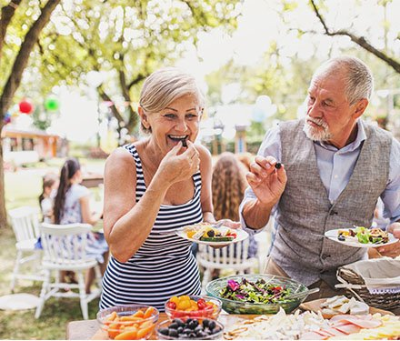 woman eating health food at an outdoor family celebration