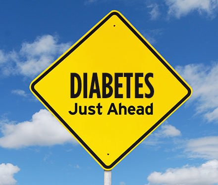 "A yellow warning street sign with the words ""Diabetes just ahead"" on it"