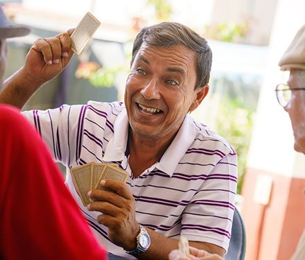 Man laughing and playing cards with his friends