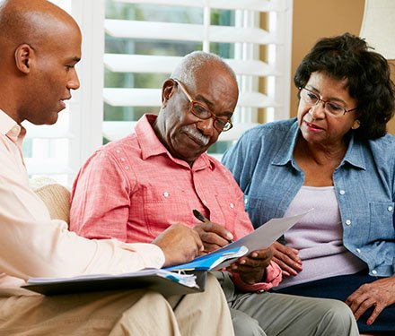 Senior adult couple sitting down on a couch in their living room going over paperwork with a business professional