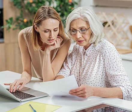 Senior adult woman and her daughter looking over paperwork together