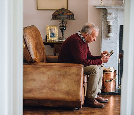 A senior adult man sitting alone in his living room looking sad as he holds a photo in his hands