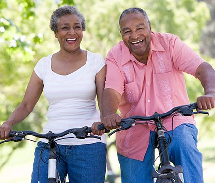 Senior adult couple laughing together as they ride their bikes on a bright sunny day
