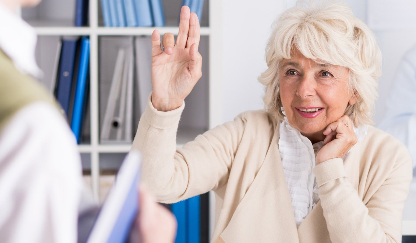Close up of a senior adult woman in a classroom raising her hand curiously with a smile